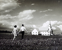 Boy and girl walking across field toward church. 1950's.<br />