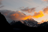 clouds hold the first light of day while hiding Mount Rainier