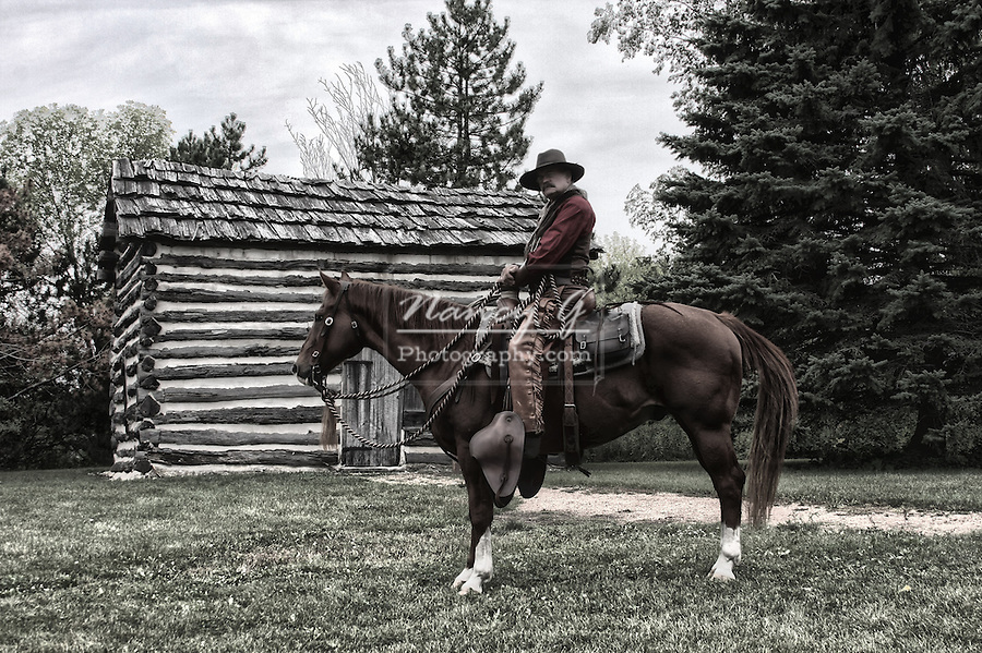 A cowboy on horseback in front of an old log cabin HDR