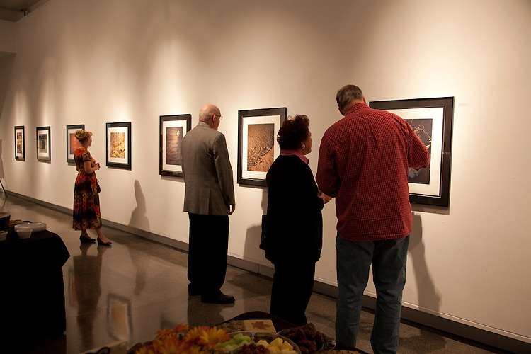 """You can see here how the gallery selections are presented, in black aluminum frames with black and white mattes. The pastel-treated prints are on torn Moab Entrada fiber paper with the edges exposed and they are hand signed and chopped with the Mark of Photopelli. Regular glass, sized 28"""" x 32."""" This image by Paul Bean on opening night at the gallery reception."""