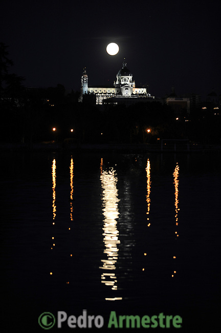 A perigee moon rises above the Almudena Cathedral in Madrid on March 19, 2011. A perigee moon is visible when the moon's orbit position is at its closest point to Earth during a full moon phase (C) Pedro ARMESTRE