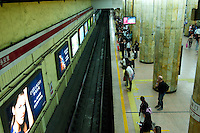 Landscape view of people standing on a subway platform in front of retail marketing signage at a B?ij?ng dìti?zhàn in D?ngchéng Q? in Beijing.  © LAN