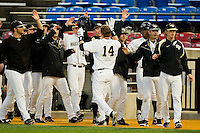 Conor Keniry #14 of the Wake Forest Demon Deacons high fives teammates after scoring a run in the bottom of the first inning against the Maryland Terrapins at Wake Forest Baseball Park on March 9, 2012 in Winston-Salem, North Carolina.  The Demon Deacons defeated the Terrapins 10-5.  (Brian Westerholt/Four Seam Images)