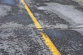 asphalt road still damp after rain fall, degrading conditions of many asphalt roads in dire need of maintenance