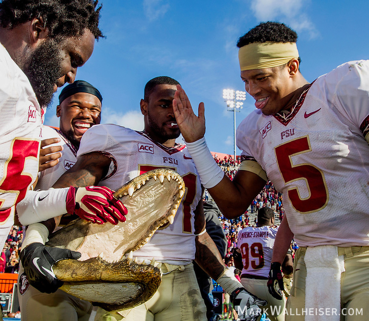 FSU quarterback Jameis Winston (5) does the Seminole Chop on a Gator head after the #2 ranked Florida State Seminoles 37-7 victory over the Florida Gators at Ben Hill Griffin Stadium in Gainesville, Florida November 30, 2013.  Florida State had an undefeated regular season at 12-0.