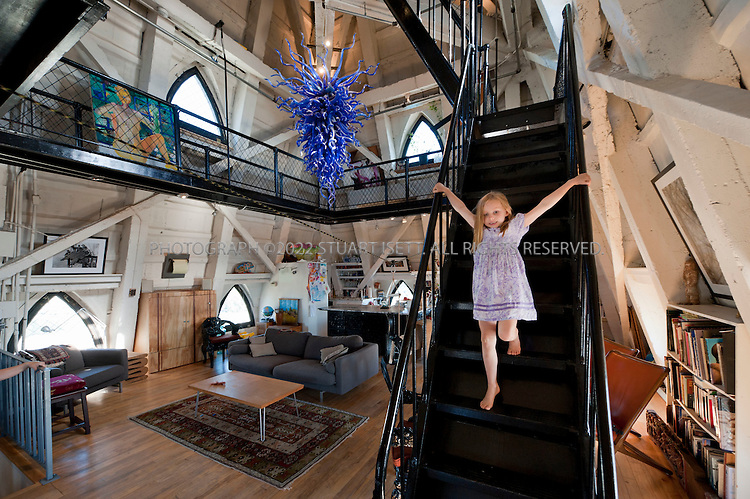 9/27/2010--Seattle,WA, USA..The main living room, kitchen and dining room on the second floor of Petra Franklin's penthouse apartment in the Smith Tower in Seattle, complete with Dale Chihuly chandelier. Here Petra's older daughter, Simone, walks down from the cat walk into the room...Smith Tower, located in Seattle's Pioneer Square neighborhood, is the oldest skyscraper in the city. Completed in 1914 it has 38 floors and  remained the tallest building on the West Coast until the Seattle Space Needle overtook it in 1962. The tower is 462 ft (143 meters) from street level to the top of the pyramid with a small glass lighthouse at the top...Petra Franklin, 46 and her husband David Lahaie, 51 live in the pyramid on top of Smith Tower with their two daughters Simone, 6, and Naomi, 3. Franklin is co-founder and general partner of Vault Capital, a venture capital fund with offices in Smith Tower...Copyright © 2010 Stuart Isett. All rights reserved.