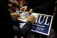 Presidential candidate Ron Paul signs a copy of the US Constitution and a campaign sign while meeting supporters at Sandy's Variety store in Manchester, New Hampshire, USA.  Paul is seeking the Republican nomination for president.