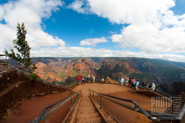 Visitors viewing the vivid colors and rock formations at Waimea Canyon, Kauai.