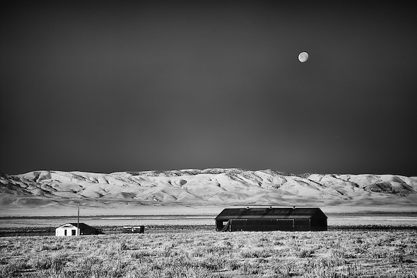 Monochrome infrared image of old barn with full moon overhead