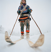 Sami reindeer herder on skis, dressed in Gakti, traditional dress, Lapland, Sweden