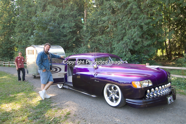 1949 purple Lincoln pulling a 2006 aluminum finish homebuilt canned ham/teardrop vintage travel trailer.