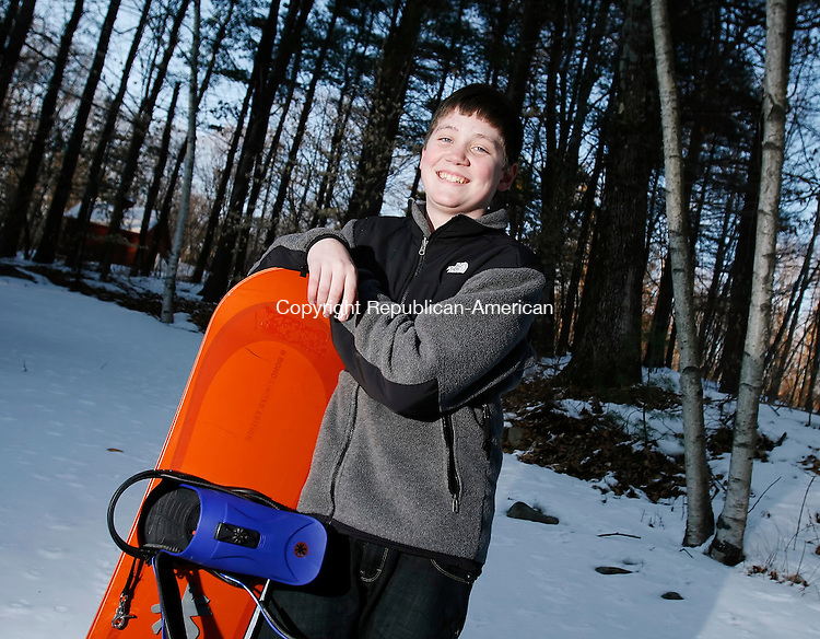 NEW MILFORD, CT, 02/04/08- 020409BZ11- Connor Wiseman, 13, poses in the yard of his New Milford home with his snowboard Wednesday.  Wisemanwas creditied with saving a 5-year-old skier who fell off a ski lift over the weekend.<br /> Jamison C. Bazinet Republican-American