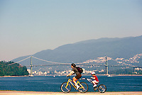 Stanley Park, Vancouver, BC, British Columbia, Canada - Mother and Child cycling on Tandem Bike on Seawall along Burrard Inlet in Summer - Lions Gate Bridge, West Vancouver, and North Shore Mountains in background