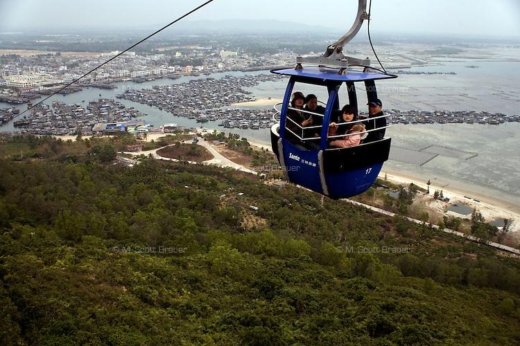 Visitors ride a gondola to Monkey Island near Lingshui, Hainan, China.