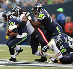 Seattle Seahawks' quarterback Russell Wilson (5) is sacked by Chicago Bears' defensive end Willie Young (97) in a pre-season game at CenturyLink Field in Seattle, Washington on August 12, 2014.  Attempting to block Young is tackle Russell Okung (76) and tackle Justin Britt (68). Seattle beat Chicago 34-6. Wilson completed 15 of 20 passes for 202 yards passed for two touchdowns and ran for another in the win. © 2014.  Jim Bryant Photo. ALL RIGHTS RESERVED