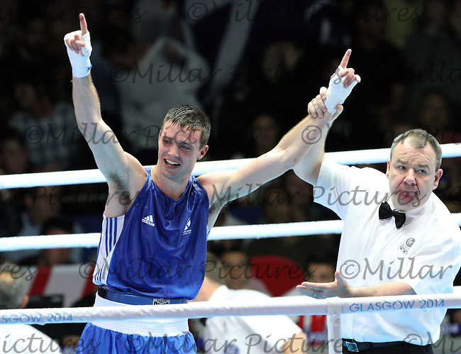 Referee Micky Gallagher of Ireland hold up the arm of Josh Taylor of  Team Scotland after he beat Samuel Maxwell of Team England in the Men's Light Welterweight Semi Final in the Boxing for the 20th Commonwealth Games, Glasgow 2014 at the Scottish Exhibition and Conference Centre, Glasgow on 1.8.14.