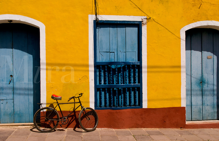 Old yellow building in colonial town of Trinidad Cuba with bike against wall
