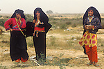 Bedouin women wearing traditional clothes scavenge for stuff where the Israeli settlement of Yamit was.  <br />