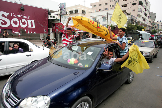 Palestinians wave with Fatah party flags during a rally celebrating the signing of a reconciliation deal in Gaza city on May 4,2011.  Hundreds of Palestinians have gathered to cheer on a unity agreement being signed in Cairo between Hamas and Fatah. Photo by Mohammed Othman