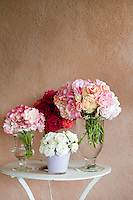 Bunches of mixed roses are arranged in simple vases on a round side table
