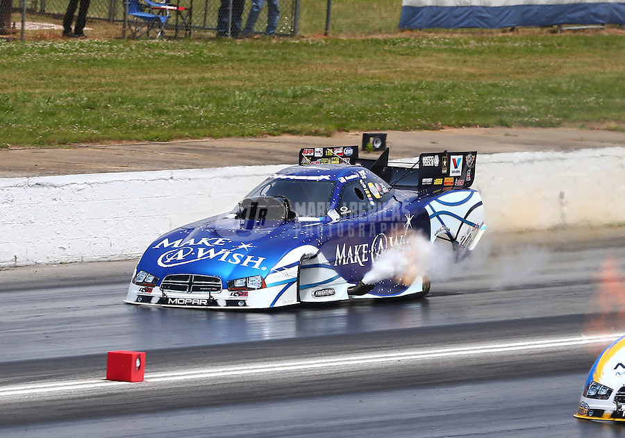 May 18, 2014; Commerce, GA, USA; NHRA funny car driver Tommy Johnson Jr moments before an explosion blows the carbon fiber body off his car during the Southern Nationals at Atlanta Dragway. Johnson was uninjured in the explosion. Mandatory Credit: Mark J. Rebilas-USA TODAY Sports