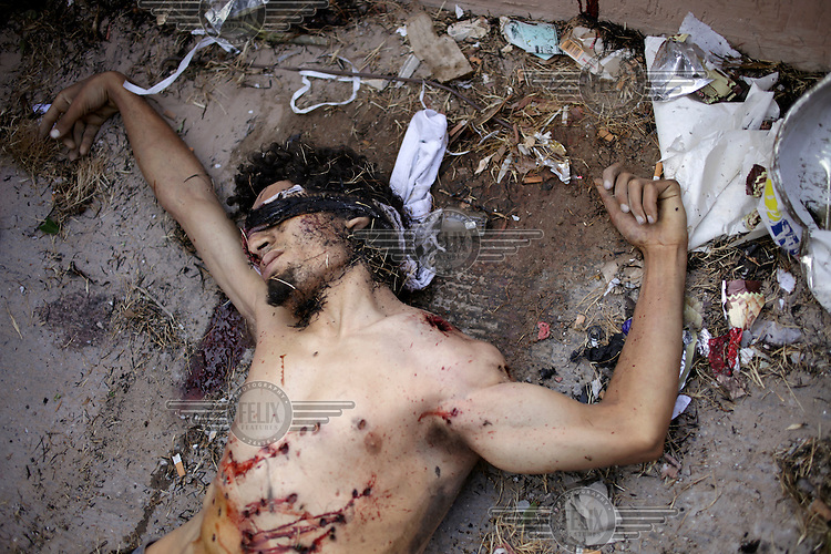The body of a rebel lies on the ground during a day of heavy fighting in Abu Salim, the final stronghold of Col. Muammar el-Qaddafi (Qaddafi) in Tripoli.