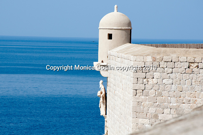 The city wall in Dubrovnik, Croatia with a view of the Adriatic Sea and a statue of Saint Blaise on the wall.