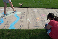 Yi Hwei Huang, a freshman marketing major from Taiwan, works with local resident Yi Hsin Lee (right) to write and decorate a famous Chinese poem on the sidewalk outside of MSU's Visual Arts Center. The sidewalk decoration was part of Thursday's [Aug. 18] Great Chalk Walk, one of many MSU Dawg Daze events.<br />  (photo by Megan Bean / &copy; Mississippi State University)