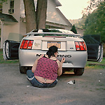 A woman in Wassaic, NY paints her Mustang with a fresh coat of black nail polish.