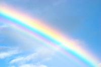Close up of a section of a double rainbow with blue sky and white clouds in the background.