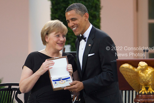 """United States President Barack Obama awards Angela Merkel, Germany's chancellor, the Presidential Medal of Freedom during a State Dinner at the White House in Washington, D.C., U.S., on Tuesday, June 7, 2011. Obama said he and Merkel agreed that the debt crisis in Europe """"cannot be allowed to put the global economic recovery at risk."""" .Credit: Andrew Harrer / Pool via CNP"""