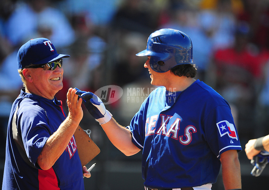 Mar. 15, 2012; Surprise, AZ, USA; Texas Rangers second baseman Ian Kinsler (right) celebrates with acting manager  Jackie Moore after hitting a home run in the fourth inning against the Oakland Athletics at Surprise Stadium.  Mandatory Credit: Mark J. Rebilas-