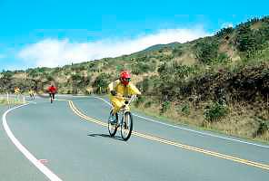 Young kids bicycling down Haleakala volcano, Maui, Hawaii