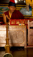 Buddhist Monk playing the ceremonial horn during a Losar chanting ceremony inside a monastery, Sikkim, India
