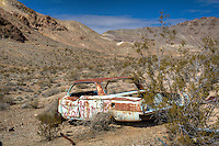 Old abandoned car in the Ghost Towm of Rhyolite Nevada.<br /> <br /> Rhyolite is a ghost town in Nye County, in the U.S. state of Nevada. It is located in the Bullfrog Hills, about 120 miles (190 km) northwest of Las Vegas, near the eastern edge of Death Valley.