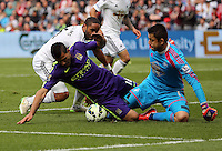 SWANSEA, WALES - MAY 17: Sergio Aguero of Manchester City (C) is stopped by Ashley Williams (L) and goalkeeper Lukasz Fabianski (R) of Swansea during the Premier League match between Swansea City and Manchester City at The Liberty Stadium on May 17, 2015 in Swansea, Wales. (photo by Athena Pictures/Getty Images)