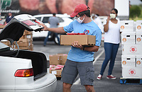 Elliot Lindsley, a volunteer, loads food Tuesday, July 28, 2020, into a vehicle at Arvest Ballpark in Springdale. The Salvation Army of Northwest Arkansas in partnership with the Church of Jesus Christ of Latter-Day Saints distributed 800 boxes of food to provide relief during the covid-19 pandemic. Both organizations have worked together nationally and saw this as an opportunity to work together locally. Donations were also contributed by The Pack Shack and Tyson Meals that Matter. The use of Arvest Ballpark was made possible by the Northwest Arkansas Naturals. For more information about the group visit nwaadoptacop.com. Check out nwaonline.com/200729Daily/ and nwadg.com/photos for a photo gallery.<br /> (NWA Democrat-Gazette/David Gottschalk)
