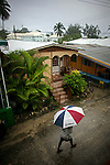 A man shields himself from the rain in Holetown in Barbados on Saturday, April 10, 2010.
