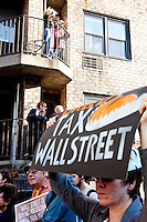 "Residents look on as thousands of people march up 6th Avenue to Times Square on October 15, 2011 in New York City in support of the ""Occupy Wall Street"" movement."
