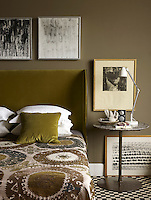 The guest bedroom is decorated in tones of brown and olive