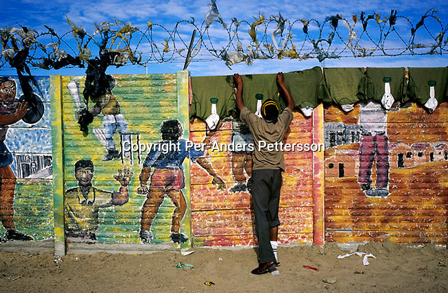 An unidentified man hangs rugby shirts that have been laundered on a colorful wall with graffiti on July 5, 2001 in Site C Khayelitsha, a township about 35 kilometers outside Cape Town, South Africa. The township has about one million people living there. Khayelitsha is one of the poorest and fastest growing townships in South Africa. People usually come from the rural areas in Eastern Cape province to find work as maids and laborers.