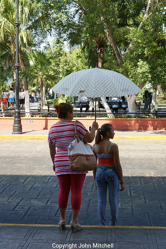 Woman and young woman waiting to cross the street in Merida, Yucatan, Mexico.