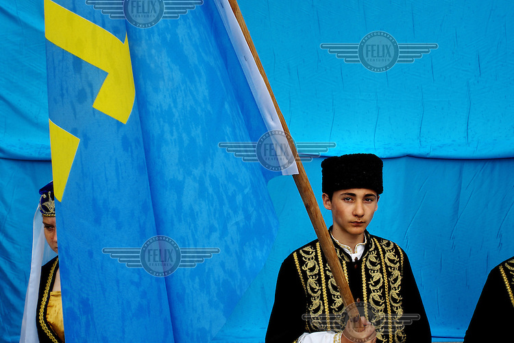 A young Crimean Tatar holds a Crimean Tatar flag during a commemoration ceremony remembering the deportation of Crimea's Tatars 70 years ago. They were deported from the region by the Soviet central authorities in 1944. The deported Crimean Tatars were resettled mainly in Central Asia. Beyond the ex-Soviet borders there are some Crimean Tatars in Romania and Turkey. Russia annexed Crimea in March following a hastily called referendum in which voters overwhelming supported the secession from Ukraine. Many Crimean Tatars opposed the annexation of Crimea and support the central authorities in Kiev.