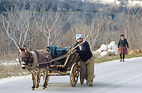 Bulgaria. Province Oblast Lovech. Lukowit. A gypsy mother couple walks on the concrete road. A donkey is pulling the cart. © 1997 Didier Ruef