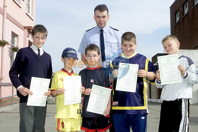 Rueben Everitt, Graham Callaghan, Mark Reilly, Damien Hoey and Richard Shelbourne, pupils from St. Joseph's CBS who recieved Garda School attandence certificates, pictured with Garda Denis Fitzpatrick..Picture Paul Mohan Newsfile