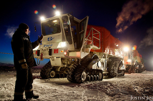 """A worker from seismic exploration company  guides an all-terrain seismic exploration vehicle in the Arctic tundra. The vehicle, called a """"vibrator"""", is made by a French company and uses seismic vibration to test the structure of the earth crust below to help prospect for oil and gas. Four billion tonnes of gas and oil have been found in the region in the last decade."""