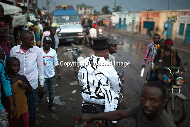 """KINSHASA, DEMOCRATIC REPUBLIC OF CONGO - FEBRUARY 12: Khaditoza Gola, the leader of the Leopard Sapeurs rides on a motorbike close to his home  on February 12, 2017 in Kinshasa, DRC. The word Sapeur comes from SAPE, a French acronym for Sociéé des Ambianceurs et Persons Élégants. or Society of Revellers and Elegant People. It also means to dress with """"elegance and style"""". Most of the young Sapeurs are unemployed, poor and live in harsh conditions in Kinshasa, a city of about 10 million people. For many of them being a Sapeur means they can escape their daily struggles and dress like fashionable Europeans. Many hustle to build up their expensive collections. Most Sapeurs could never afford to visit Paris, and usually relatives send or bring clothes back to Kinshasa. Mr. Khaditoza has one of the largest collections of clothes, shoes and accessories of all Sapeurs. (Photo by Per-Anders Pettersson)"""