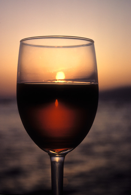 Glass of Cabernet Sauvignon with sunset reflected in glass