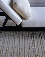 The oat-grey wool carpet provides a perfect background for the dark wood of the daybed