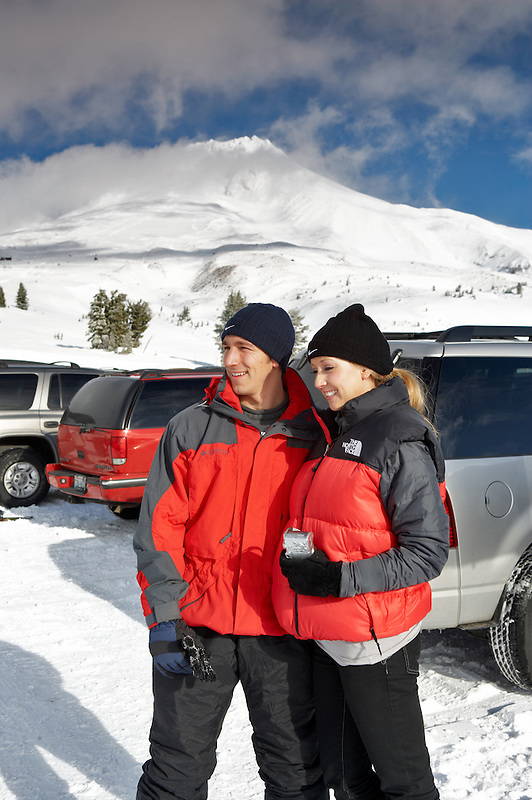 Man and woman in parking lot of Timberline Lodge in winter with Mt. Hood